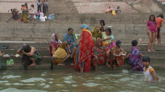 Sari-clad women in mourning bathe themselves in the Ganges River.