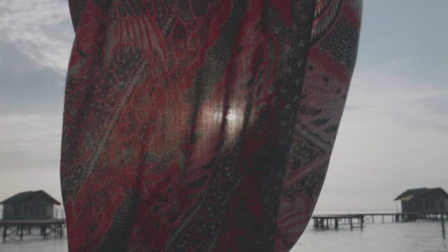 stockvideo's en b-roll-footage met a sarong blowing in the wind on a deck over water. - sarong