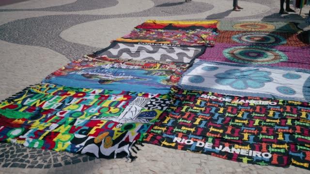 vídeos de stock, filmes e b-roll de cangas e toalhas para venda na praia de copacabana - vendendo