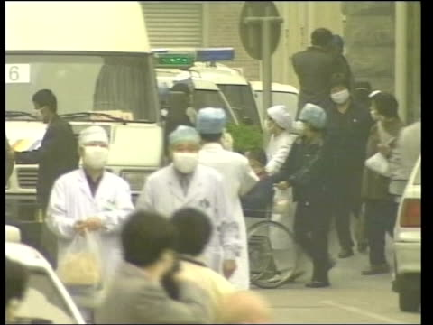 sars outbreak; itn china: beijing: ext lms patient wheeled from hospital after it was cleared to treat sufferers of severe acute respiratory disease... - 重症急性呼吸器症候群点の映像素材/bロール
