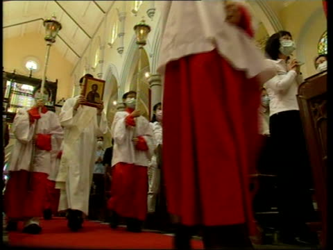 china admits epidemic worse than reported; itn china: hong kong: int church choir boys up central aisle of church towards congregation members... - 重症急性呼吸器症候群点の映像素材/bロール
