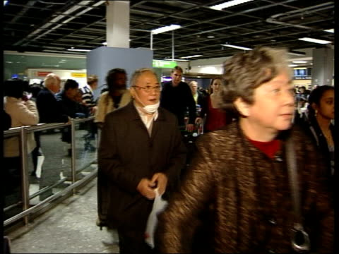 government may toughen policy; itn england: london: heathrow airport: passengers arriving from china with face masks - severe acute respiratory syndrome stock videos & royalty-free footage