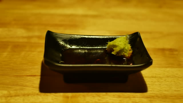 sashimi is often served with wasabi, and soy sauce-dan - wasabi sauce stock videos and b-roll footage