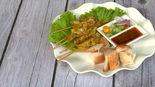 satay pork marinated with yellow spices, dressed on a skewer, grilled until cooked eaten with sauce mayard and toast bread - marinated stock videos & royalty-free footage