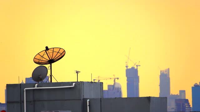 4k: satellit parabolantenn och solnedgång på bangkok city - radio och tv utsändning bildbanksvideor och videomaterial från bakom kulisserna