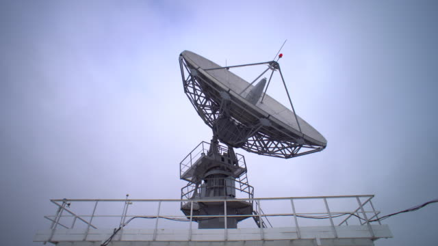 a satellite dish moves in time-lapse and is silhouetted against the sky - radar stock videos and b-roll footage
