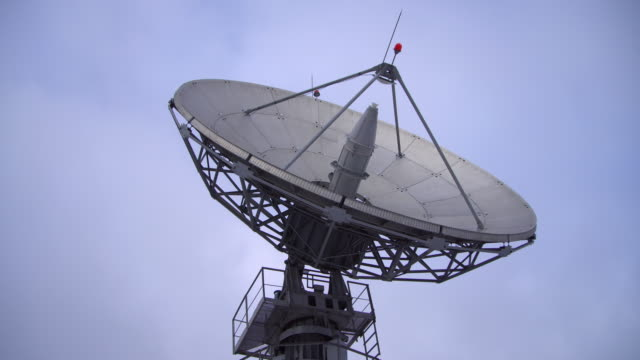 a satellite dish moves in time-lapse and is silhouetted against the sky - broadcasting stock videos & royalty-free footage
