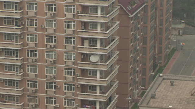 MS Satellite dish on balcony of apartment building/ ZO HA WS Building against foggy sky/ Beijing, China