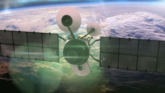 satellite in orbit around the earth. - satellitenschüssel stock-videos und b-roll-filmmaterial