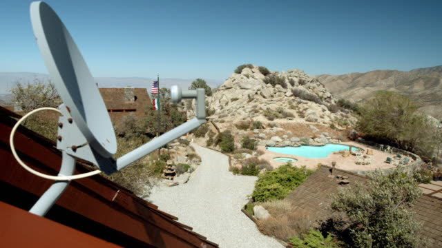 ws pan satellite tv dish mounted on guest house roof overlooking frank sinatra's 1970 mountain retreat with main house, swimming pool and tennis court - satellite tv stock videos and b-roll footage
