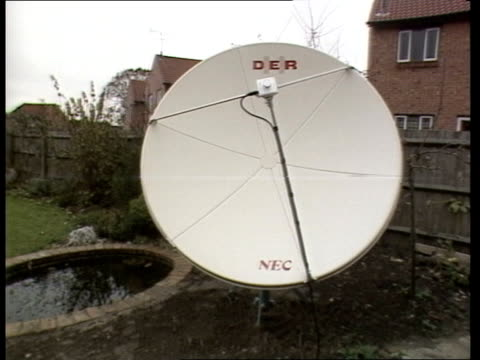 Satellite TV in Britain LIB Surrey Woking EXT MS Satellite dish by shed PULL MS Dish with 'Der' on it / LA TV aerial on roof PULL OUT to satellite...