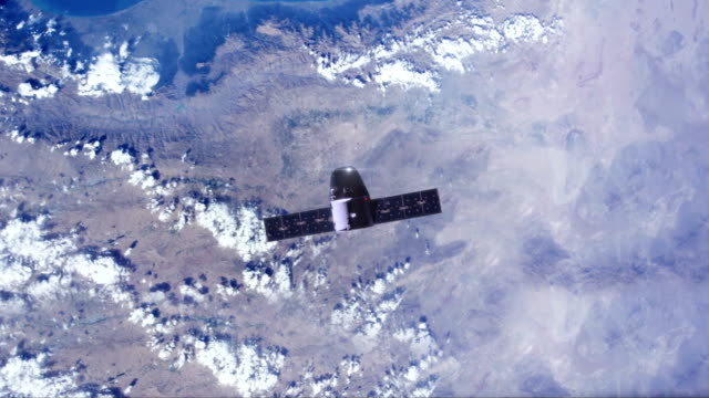 satellite with solar panels moving over earth - moving past video stock e b–roll