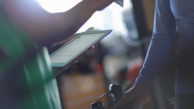 Satisfied customer shakes hands with bike shop worker holding tablet