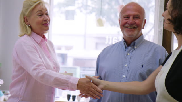 satisfied customers shaking hands with pottery owner - artist stock videos & royalty-free footage