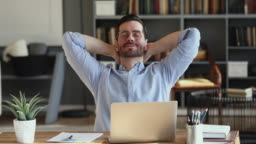 Satisfied employee relaxing at office desk holding hands behind head