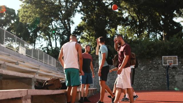 vídeos de stock, filmes e b-roll de jogadores felizes de basquete satisfeitos rindo no campo de basquete após sessão de treinamento no dia ensolarado de verão - hobbie