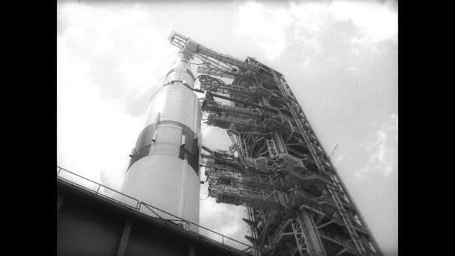 saturn rocket ship ready to be moved at cape kennedy / workers in hardhats mill about base where rocket is on caterpillar style platform that moves... - ship launch stock videos and b-roll footage
