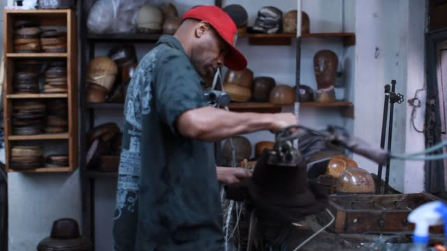 Satya Twena is a hat designer with a factory located in the Fashion District of Manhattan on February 24 Wide shot of middle aged male African...