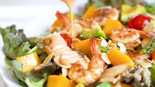 slo mo sauce pours on mango quinoa and shrimp salad dish. - salad dressing stock videos & royalty-free footage