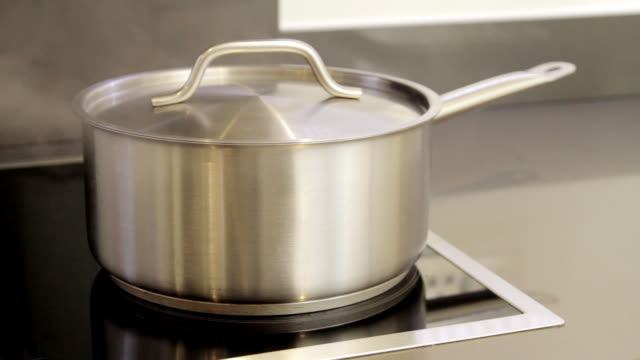 CU saucepan of boiling water on hob letting off steam