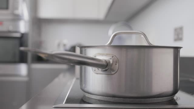 saucepan  on hob - lid stock videos & royalty-free footage