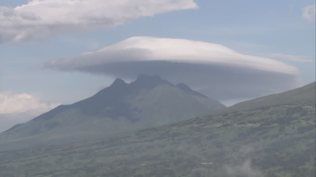 a saucer-shaped cloud casts a shadow over sabinyo in the virunga mountains. available in hd. - nationalpark stock-videos und b-roll-filmmaterial