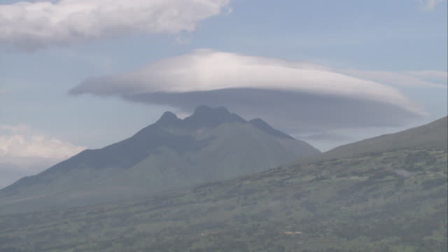 A saucer-shaped cloud casts a shadow over Sabinyo in the Virunga Mountains. Available in HD.
