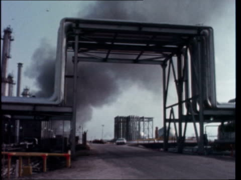saudi arabia oil saudi arabia ras tanura ms flame burns pull out gv storage tanks gv pan refinery lr ms reflection in water tilt pipes ms pipes ms... - peter snow stock-videos und b-roll-filmmaterial