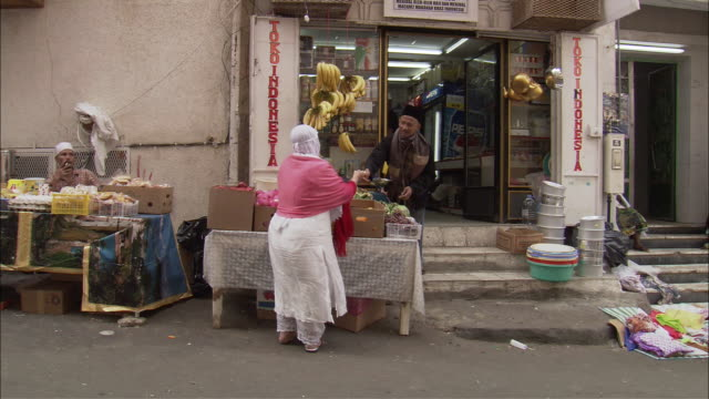 a saudi woman buys produce from a street vendor as other shoppers pass by. - サウジアラビア点の映像素材/bロール