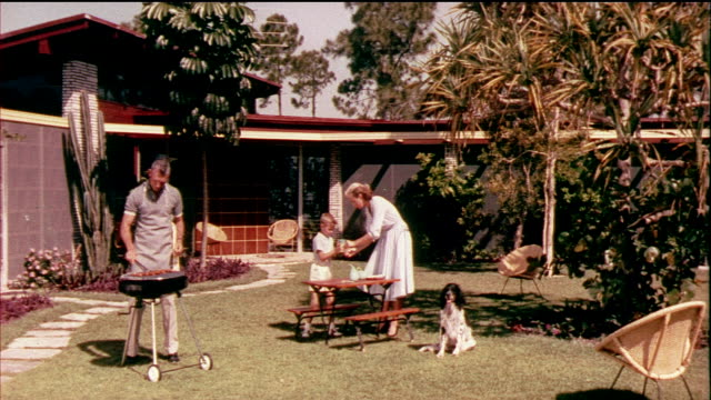 1958 MONTAGE HA ZO MS WS sausages cooking on barbecue grill, family of four barbecuing in back yard / USA / AUDIO