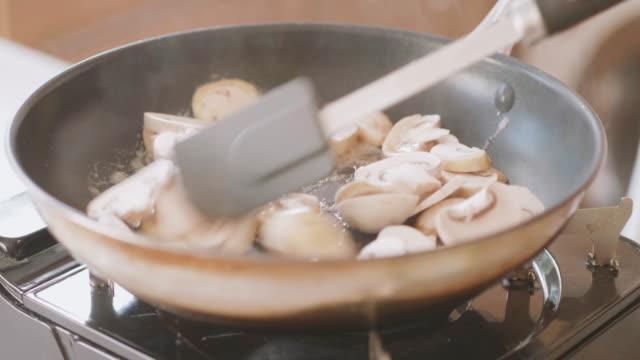 フライパンに白いキノコを炒める - キャンプ用ストーブ点の映像素材/bロール