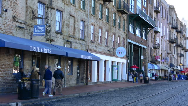savannah georgia tourists people walking on riverwalk on river street with shopping and shops in old buildings - savannah georgia stock videos & royalty-free footage