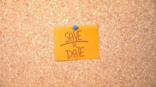save the date writed paper pinning up on corkboard - blocco per appunti video stock e b–roll