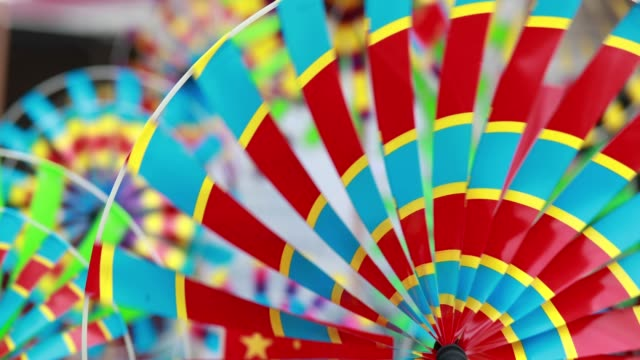 save to board close-up shot of rotating colorful windmill toy in row - girandola video stock e b–roll