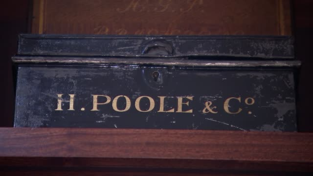 savile row tailors henry poole open up archives 'h poole co' metal box on shelf low angle view alphabetised ledger books on shelves - savile row stock videos and b-roll footage