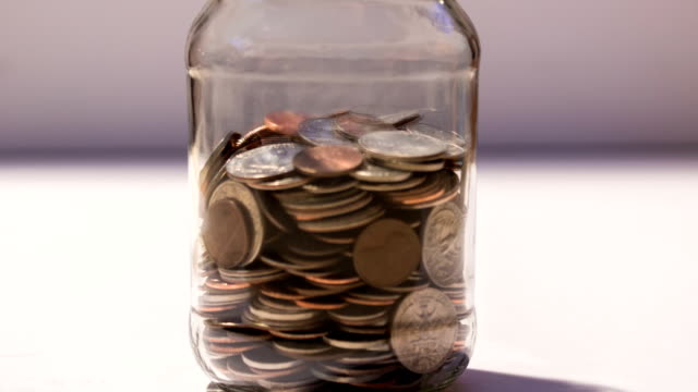 saving jar of money filling up with coins - coin stock videos and b-roll footage