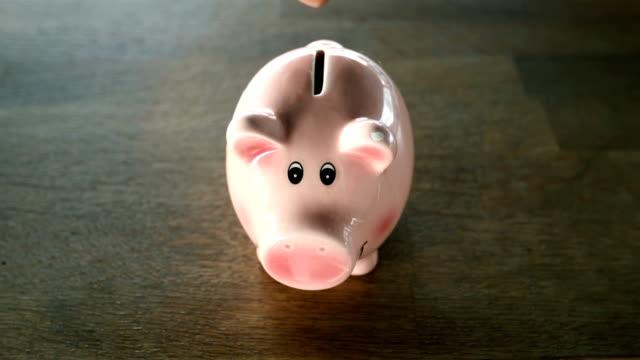 vídeos de stock, filmes e b-roll de economizando dinheiro para o futuro em moneybox com copyspace - poupança