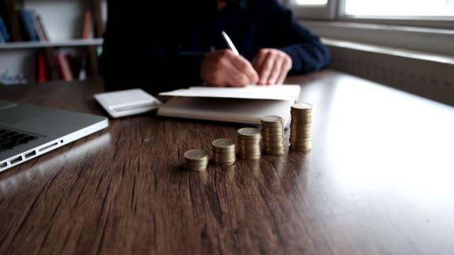 spara pengar man hand sätta mynt stack koncept affärs ekonomi - skuld finansväsen bildbanksvideor och videomaterial från bakom kulisserna