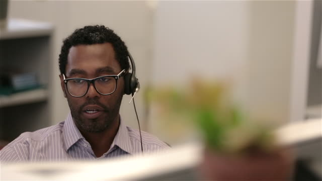 savvy office worker pitches to client on headset (dolly shot) - button down shirt stock videos & royalty-free footage