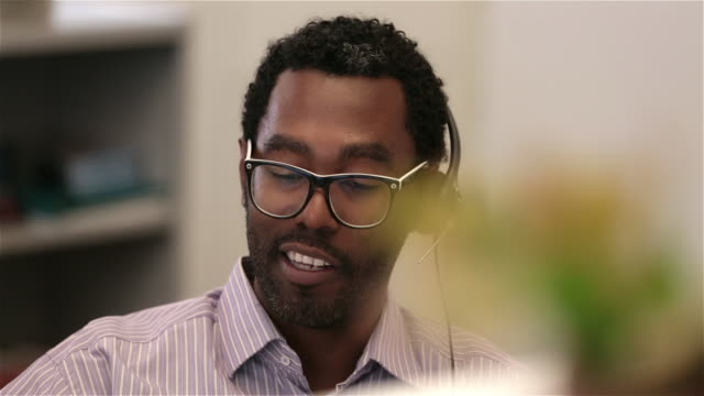 stockvideo's en b-roll-footage met savvy office worker talks to client on headset, gives thumbs up (dolly shot) - headset