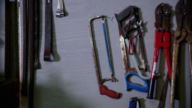 vídeos de stock, filmes e b-roll de cu saws hanging on wall in workshop, live oak, florida, usa - grupo médio de objetos