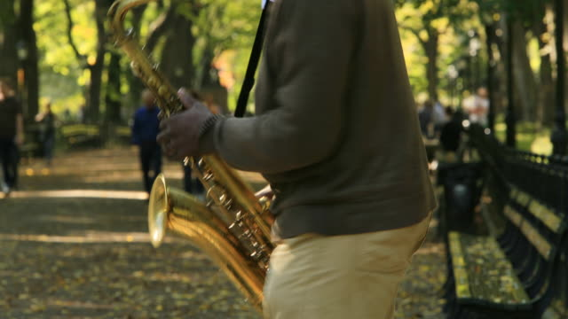 saxophone player in the park - saxophone stock videos and b-roll footage