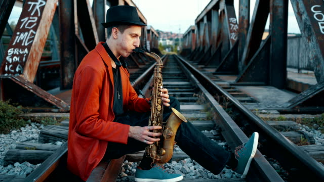 saxophone player sitting on railroad track - saxophone stock videos & royalty-free footage
