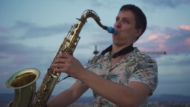saxophonist performing his solo performance in sunset on rooftop - passion stock videos & royalty-free footage