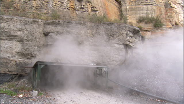 vídeos de stock, filmes e b-roll de scaffold covered appalachian mountains rockface mine opening w/ gray/white smoke rising out of entrance no people possibly coal fire methane gas... - appalachia
