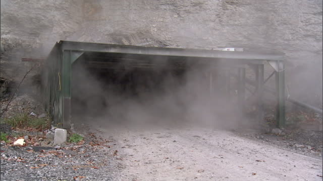 Scaffold covered Appalachian Mountains rockface mine opening w/ gray/white smoke rising out of entrance No people Possibly coal fire methane gas...
