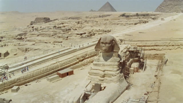 AERIAL WS Scaffolding around Great Sphinx with Giza Pyramids in background / Giza, Egypt