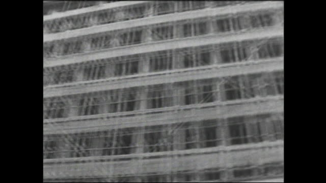 scaffolding lines the facade of an office building under construction in japan. - 戦後点の映像素材/bロール