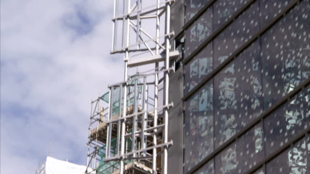 scaffolding stands against a style building at a construction site. available in hd. - slate rock stock videos and b-roll footage