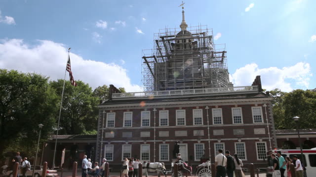 la scaffolding surrounding the bell tower of independence hall with traffic and pedestrians passing in front / philadelphia, pennsylvania, united states - independence hall stock videos and b-roll footage